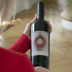 Personalised Christmas Wine. Christmas Wreath Red Wine with personalised message on the label presented in a buff brown box on a bed of shred.